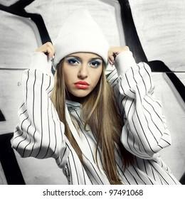 Fashion portrait of beautiful hip-hop woman posing on bright wall