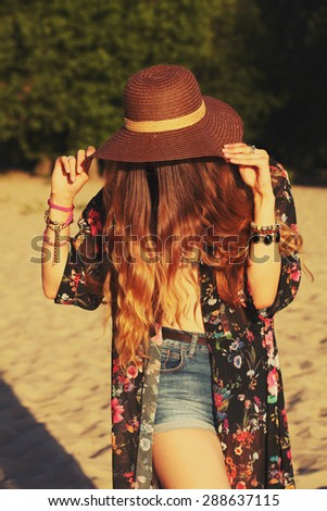 11ddbd9c8b59 Fashion portrait of beautiful hippie young woman wearing boho chic clothes  and summer hat outdoors.