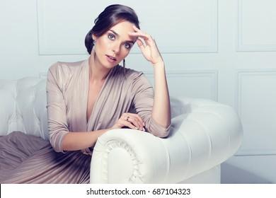 Fashion portrait of beautiful lady in gold evening dress. Elegant hair, makeup, earrings