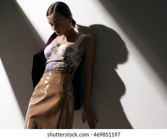 fashion portrait of beautiful lady in leather skirt looking down . studio location near the white wall with dark shadow.