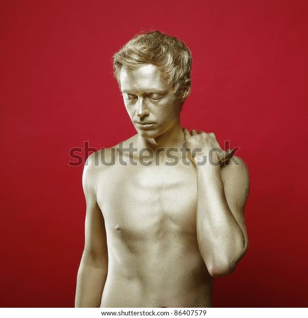 Fashion portrait of beautiful man with golden body art