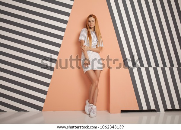 Fashion portrait of beautiful red haired fashion model girl with long hair in summer clothing over modern background