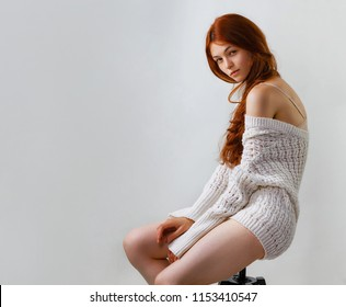 Fashion portrait of beautiful redhead woman dressed in knitted sweater looking over shoulder while posing on grey background sitting on a chair, copy space.