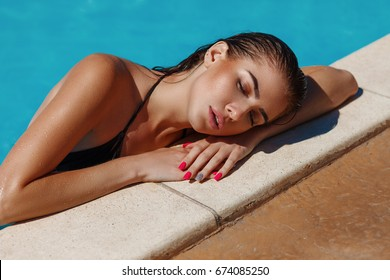 Fashion portrait of beautiful sexy tanned sporty slim woman relaxing in swimming pool spa. Fit figure with nice shapes. Hot summer day and sunny light. Lifestyle luxury tropical vacation concept.
