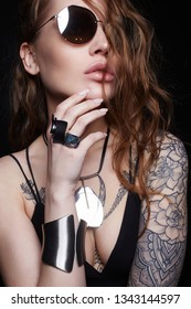 fashion portrait of Beautiful sexy woman with tattoo. beauty tattooed girl in sunglasses and bracelet