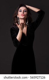 Fashion portrait of a beautiful sexy woman in black velvet dress blowing a kiss on a grey background