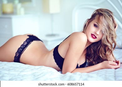 Fashion portrait of beautiful sexy young adult blond woman model wearing black erotic lingerie lying on white bed in the morning