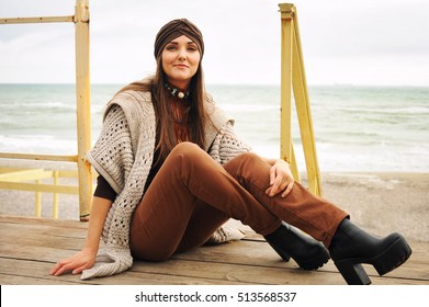 Fashion portrait of a beautiful smiling brunette woman sitting in front of town beach, smiling and looking at camera, fashion autumn outfit, large shoes with heels, hat and cardigan