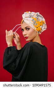 Fashion portrait of a beautiful, tall and fashionable woman of Middle Eastern descent. She is posing against a red, plain background.