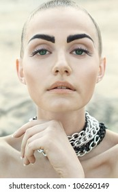 Fashion portrait of beautiful woman with chained neck posing on light full background