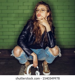 Fashion portrait of beautiful woman DJ in cool glasses, rock black leather jacket slav squat sit and with white music headphones sound. Hipster urban style girl. Lifestyle outdoor city portrait.