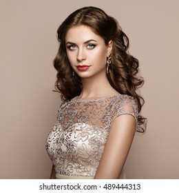 Fashion portrait of beautiful woman in elegant dress. Girl with elegant hairstyle and jewelry