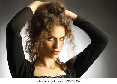 Fashion portrait of beautiful woman elegant brunette with hands on the brown hair
