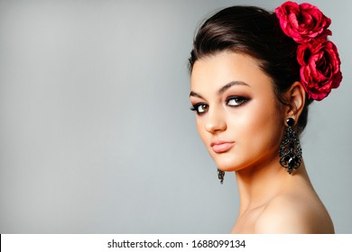 Fashion portrait of beautiful woman with pink flowers in her hair. Spring calendar miss April.