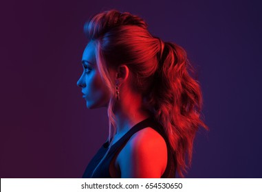 Fashion portrait of beautiful woman profile. Colorful light.
