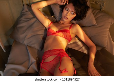 Fashion portrait of beautiful woman in sexy stylish lingerie. Model with perfect sensual figure pose in home interior. Sexy lady in classic room with sunny light. Morning in bedroom.