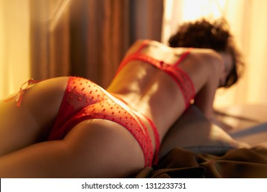 Fashion portrait of beautiful woman in sexy stylish red lingerie. Model with perfect sensual figure pose in home interior. Sexy lady in classic room with sunny light. Morning in bedroom.