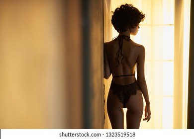Fashion portrait of beautiful woman with sexy stylish lingerie. Model with perfect sensual figure pose in home interior. Sexy lady in classic room with sunny light. Morning in bedroom.