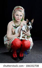 Fashion portrait of beautiful woman with small dog