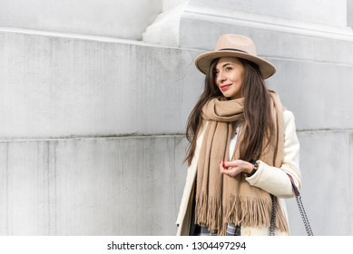 c80f89a3f72 Fashion portrait of beautiful woman stands near the gray wall. Wearing  stylish bright coat