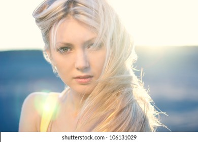 Fashion portrait of beautiful woman with streaming hair posing on sunny background