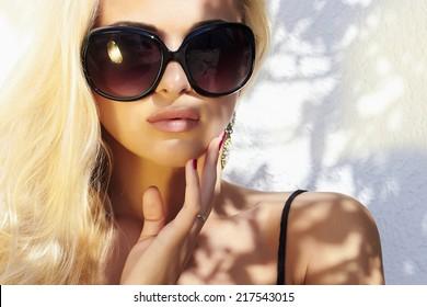 fashion portrait of beautiful woman in sunglasses.beauty blond girl in near the wall. Summer