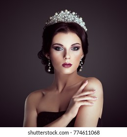 Fashion Portrait of Beautiful Woman with Tiara on head. Elegant Hairstyle. Perfect Make-Up and Jewelry. Red Lips