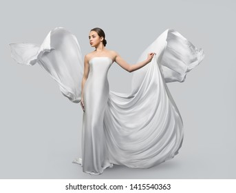 Fashion portrait of a beautiful woman in a waving white dress. Light fabric flies in the wind. Light gray background. Girl posing in studio