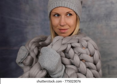 Fashion portrait of beautiful woman wearing in knitted hat and gloves holding gentle, soft merino wool blanket. Cozy winter style.
