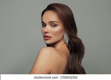 Fashion portrait of a beautiful young brunette with wavy hair. Beautiful woman with clean skin on her face. Beauty, cosmetics and cosmetology. Fashion earrings as accessories