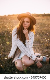 Fashion portrait of beautiful young pretty girl with hippie outfit and hat outdoors in the field at sunset. Soft warm color tone. Boho lifestyle. Bohemian Style. Vertical with blank space for text