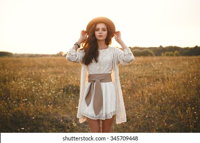 Fashion portrait of beautiful young pretty girl with hippie outfit holding hat outdoors at sunset. Soft warm vintage color tone. Boho lifestyle. Bohemian Style. Horizontal with blank space for text