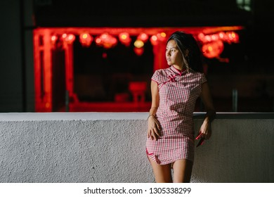 Fashion portrait of a beautiful, young and sexy Asian Chinese model wearing a cheongsam qipao dress. She is leaning on a ledge with red Chinese lanterns in the background.