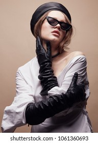 Fashion portrait of beautiful young woman in black leather beret cap, white shirt and cat eye retro sunglasses