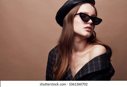 Fashion portrait of beautiful young woman in black leather beret cap, plaid jacket and cat eye retro sunglasses with massive golden earrings