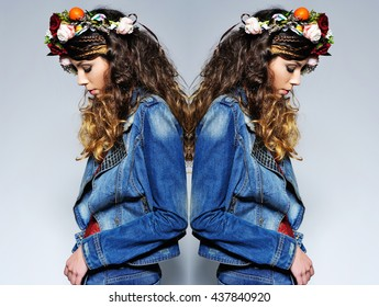 Fashion portrait of a beautiful young woman with gipsy hairstyle wearing handmade statement flower crown and trendy jeans outfit