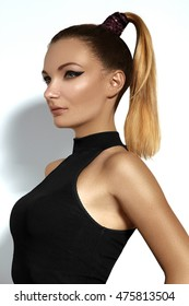 Fashion portrait of beautiful young woman with ponytail hairstyle. Beauty shot of sexy girl on white background. Pony tail straight hair, catwalk black eyeliner makeup on model face