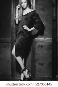 Fashion portrait of beautiful young woman in sexy black dress near with wood wall. Elegant dark evening look. Pretty lady with blond straight hair. Glamour style for luxury life