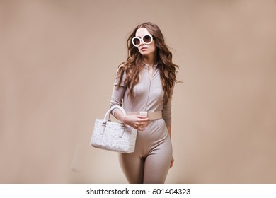 Fashion portrait of beautiful young woman in a  sunglasses, handbag.