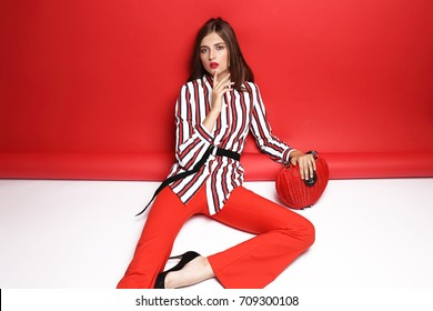 387611a63 Fashion portrait of beautiful young woman. Red pants, red handbag, blouse,  bright