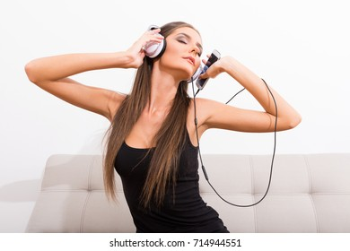 Fashion Portrait of a beautiful young woman listening to music with headphones while sitting on the sofa