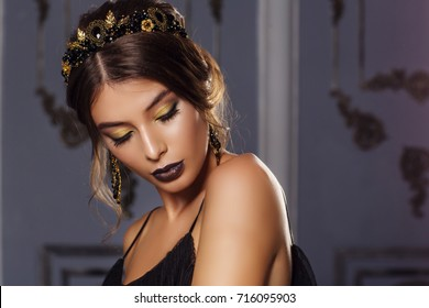 Fashion portrait of a beautiful young woman with a black jewelry