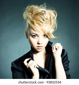 Fashion portrait of beautiful young woman posing on black background with modern styled hair