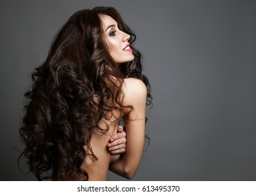 Fashion portrait of beautiful ypung woman with long curly healthy hair over grey background. Studio photo