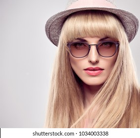 Fashion Portrait Beauty Sensual Blond Woman in Stylish Sunglasses. Shiny straight hair, Blue Eyes. Trendy Bang Hairstyle. Portrait Glamour Beautiful Model Girl in fashionable Hat
