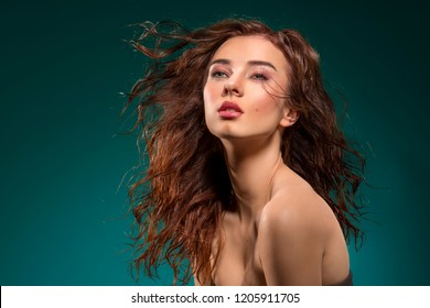 fashion portrait of beuty brunette girl with wavy, flying wet hair. Posing with sensual expression and and cute make-up on green