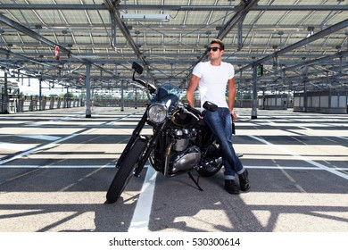 Fashion portrait of biker man wearing a white shirt, blue jeans and sunglasses sitting on his classic motorcycle in a empty car parking