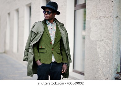 Fashion portrait of black african american man on green velvet jacket, black hat and coat cloak on his shoulders walking on streets of city background house with many windows