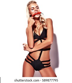 fashion portrait of blond model in summer black swimwear clothes posing near pink wall, biting red chilli pepper