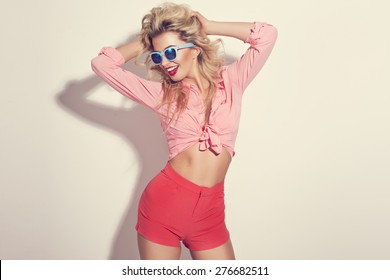 Fashion portrait of blonde girl with sunglasses wearing pastel stylization